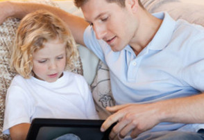 Father and son using tablet on the sofa together